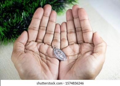 Girl Hands Holding Miraculous Medal and Praying to Our Lady Holy Mary, Mother of God.