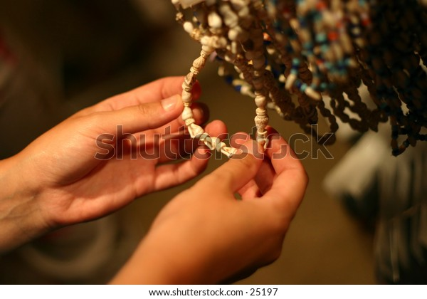 Girl hands holding a necklace made out of sea shells