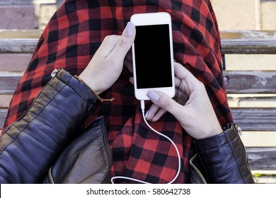 girl hands holding a phone with headphones connected.