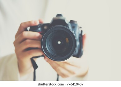 Girl hands holding photo camera with vintage color effect, white background, copy space.