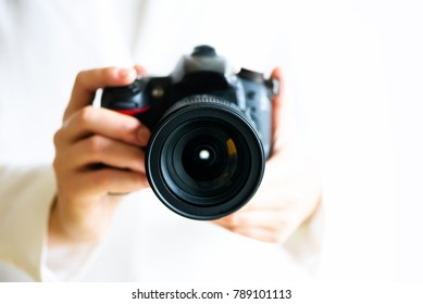 Girl hands holding photo camera, white background, copy space. Travel and shoot concept.
