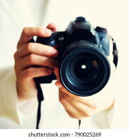 Girl hands holding photo camera, white background, copy space. Travel and shoot concept. Square crop.