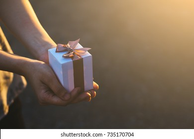 Girl hands holding a small gift wrapped with pink ribbon. Small gift in the hands / concept give happiness
