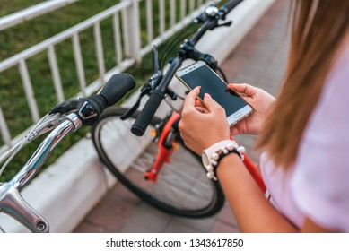 The girl in the hands holds the phone, selects the map application online to the Internet, search for a route around city in the summer on a bicycle.