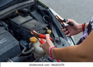 Girl hands with jump cables. Car broken. No power.