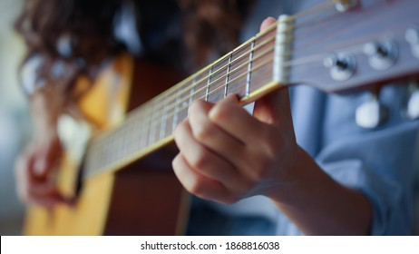 Girl hands playing acoustic guitar. Female musician creating music with string instrument. Unrecognizable woman recording guitar sound on smartphone. Guitarist fingers strumming strings on guitar