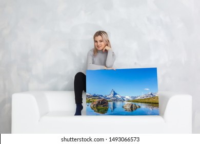 Girl hanging a frame canvas on a gray wall