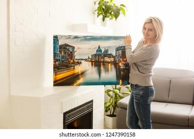 Girl hanging a frame on a wall, sun light
