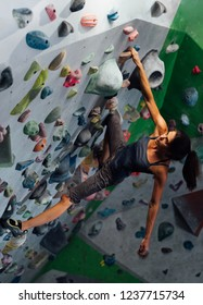 the girl hangs on the ledges climbing the wall in the training room