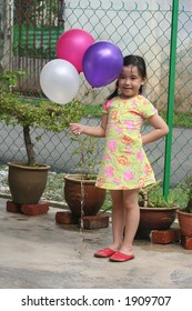 Girl happily holding colorful balloons