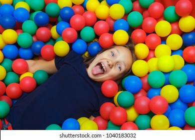 girl is happy in a dry pool with balls