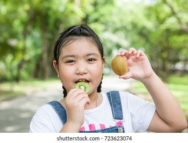 The girl is happy to eating fruit in the garden in the summer time.