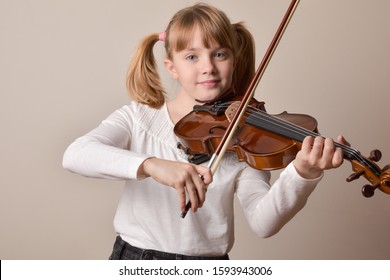 Girl happy looking straight ahead playing the violin. Horizontal composition. Front view.