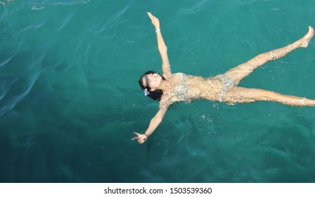 Girl happy and sweetheart swims in the sea with long flowing hair