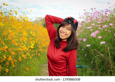 The Girl is happy to travel in colorful cosmos flower field