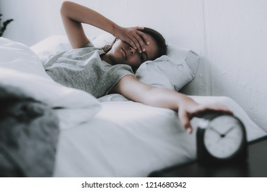 Girl Hardly Awakes and Pulls Alarm Off in Morning. Cute Black-haired Caucasian Child Wearing GrayT-Shirt Sleeps Near Alarm in Bed With White Linens Keeps Hand on Head. Morning Concept