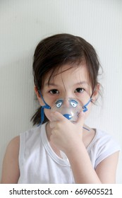 Girl has asthma and need nebulizations,Sick girl inhalation therapy by the mask of inhaler.Girl has a nasal congestion because of a cold.Girl making inhalation with nebulizer. Close up with copy space