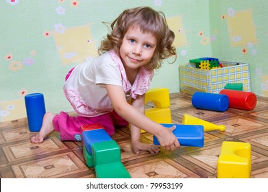 The girl has built a tower out of blocks, the interior