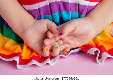Girl has colorful nails, kid fashion. Holding hands behind the back