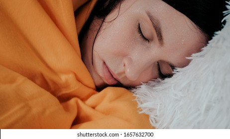 Girl has fever. Young attractive Caucasian woman lies on bed of her shakes. Colds, flu, cold sweat, virus, acute respiratory illness, chills concept. Close-up