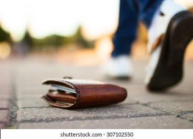 Girl has lost her wallet with money on city street at sunny summer day. Close-up shot of brown leather wallet laying at sidewalk, and feet of woman going away on the background. Concept of money loss