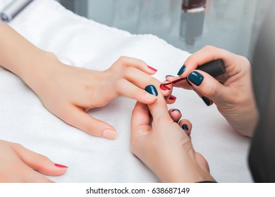 Girl has a manicure and paint nails with lacquer in the beauty salon