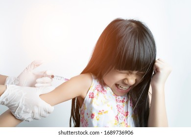 The girl has a painful face of being vaccinated for treatment and prevention by a doctor or nurse with a white background.