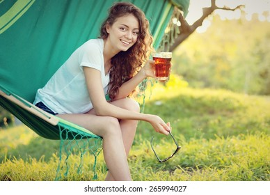 girl has a rest in a hammock with a drink