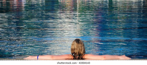 The girl has a rest in pool. The rear view