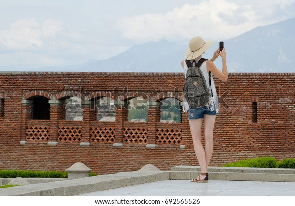 Girl in a hat with a backpack photographing an old fortress. View from the back