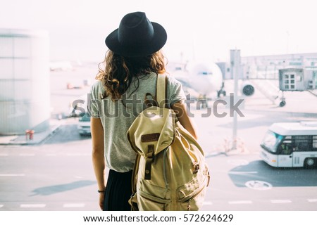 Girl in hat with backpack traveling in the airport