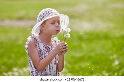 Girl in hat blowing blowball at field
