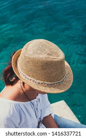 Girl with a hat by the sea