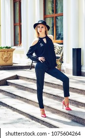 Girl in hat and classic high-heeled shoes. Model posing on the street. Fashionable woman in the city