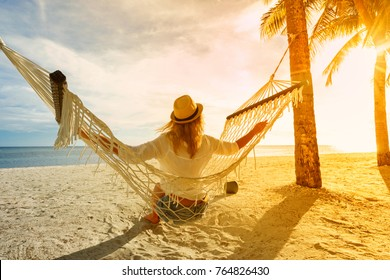 Girl in hat with coconut sitting on hammock on the beach and enjoying sunset.