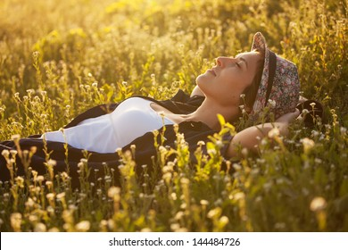 The girl in a hat dremet among wildflowers at sunset