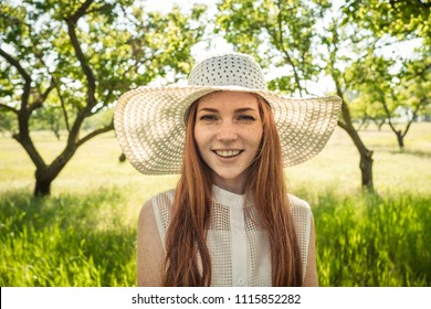 Girl in the hat and dress of the garden trees. red-haired young woman with freckles on vacation