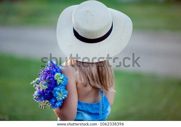 A girl with a hat and flowers is standing with her back