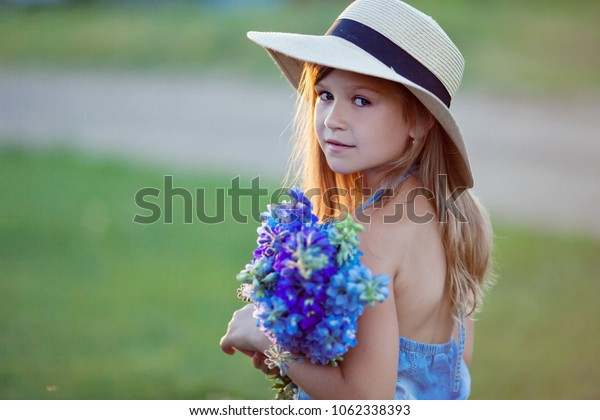 Girl in hat and with flowers at sunset