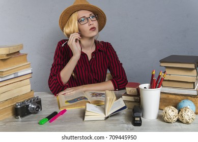 girl in a hat and glasses reads books