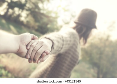 girl with hat holding boyfriend hand love concept