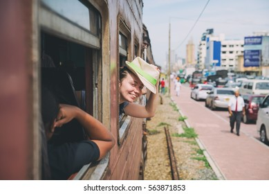 girl in a hat looking out the train window