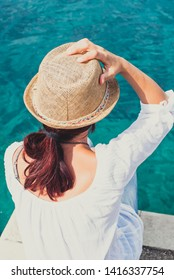 Girl with hat looking at the sea
