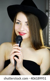 girl in a hat with a microphone in his hands