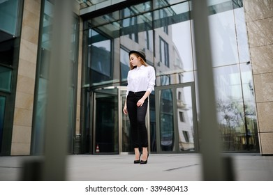 girl in a hat on a background of glass building