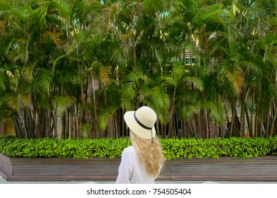 Girl in a hat on a background of palms in Macau, China.