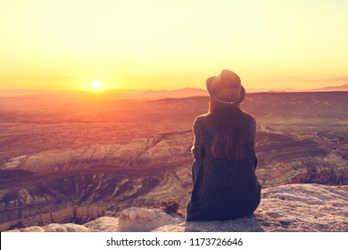 A girl in a hat on top of a hill in silence and loneliness admires a tranquil natural landscape in search of a soul.