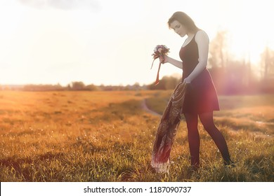 A girl in a hat on a walk in the park. A girl with a basket walks in autumn. Girl is walking along the road at sunset.