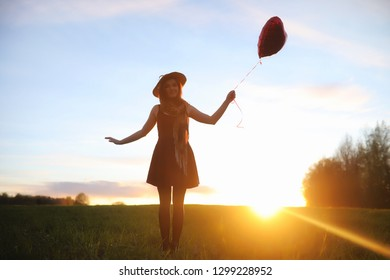 A girl in a hat on a walk in the park. A girl with a basket walks in the spring. Girl is walking along the road at sunset.