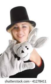 Girl in hat, with rabbit puppet on her hand. Focus on rabbit.